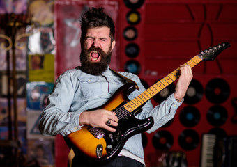 Rock singer concept. Musician with beard play electric guitar instrument.