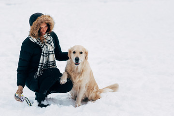 Image of smiling girl with dog in winter park