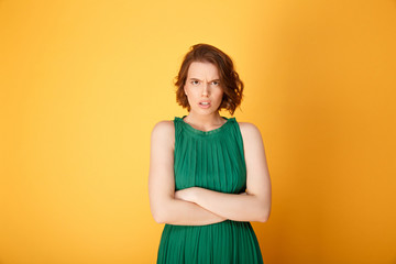 portrait of angry woman with arms crossed looking at camera isolated on orange