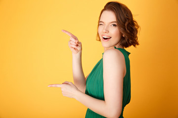 side view of attractive winking woman pointing away isolated on orange