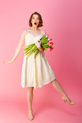 young emotional woman in white dress with bouquet of pink spring tulips isolated on pink