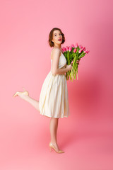 side view of young woman in white dress with bouquet of pink tulips isolated on pink