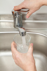Glass in female hand is filled with clean transparent water under the tap