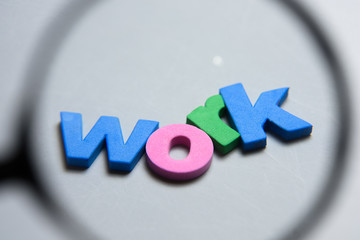 WORK, word written on white background with colorful letters under magnifying glass.