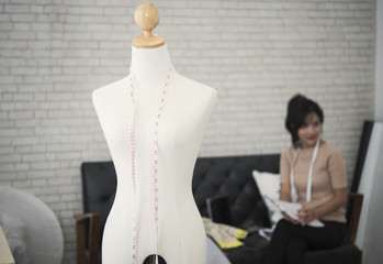Young female designer fashion working for seamstress garment.