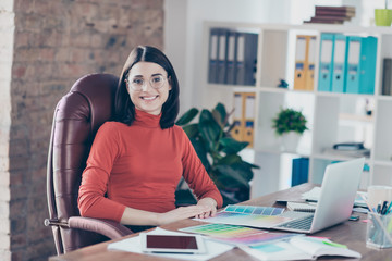 Lifestyle red sweater armchair boss studio spects tone fashion project indoors illustration workplace workstation employment education people person concept. Excited short-haired retoucher sits table