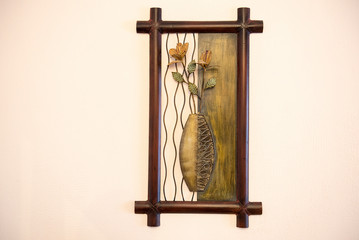 Vase with flowers. Art creation from metal and wood on the wall.