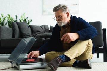 stylish senior man in eyeglasses putting vinyl record in turntable while sitting on carpet