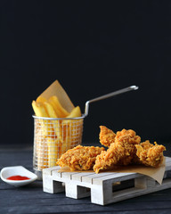 Crispy chicken strips with spicy ketchup in ramekin and french fries in a fancy support on a wooden plate. Dark background. Junk food concept.