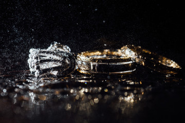 Wedding rings and earrings are wet, with drops. Reflections on the glass are professional.