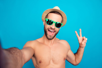 Self picture of naked, successful bachelor, attractive, funny, comic guy, ladies' man shooting selfie  and showing v-sign with open mouth, shouting, screaming, having video call over blue background