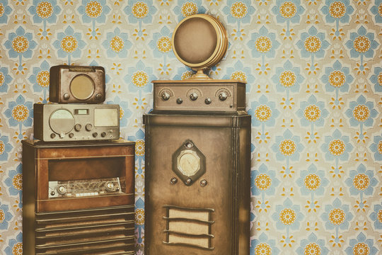 Old radio's in front of a retro wallpaper with flower pattern