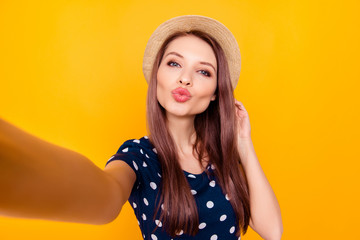 Self portrait of nice, amazing, pretty, charming, sexy woman shooting selfie with hand on front camera, blowing air kiss with pout lips, having polka-dot outfit, isolated on yellow background