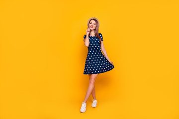 Full-length, fullbody portrait of nice, cheerful, positive, cute girl holding hands on bottom of polka-dot dress and touching her face, making step front, standing over yellow background