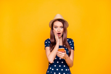 Charming, amazed, impressed by photo, video, information, news, pretty girl in polka-dot outfit having, using smart phone, holding palm on cheek with wide open eyes and mouth looking at screen of tel