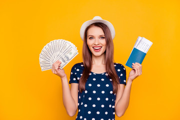 Portrait of cheerful, happy, pretty, charming, laughing girl polka-dot t-shirt with hat on head, having money fan and passport with tickets in raised hands, isolated on yellow background