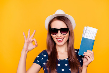 Close up portrait of charming, pretty, professional tour operator in glasses with white hat on head having passport and flying tickets in hand, gesture ok sign, isolated on yellow background