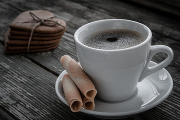White cup of coffee on a natural old wooden background with biscuits. Selective focus. With copy space