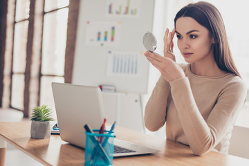 Portrait of attractive charming pretty tender gentle fresh carefree stunning elegant gorgeous employer correcting doing make up looking in mirror touching brows sitting at modern light office