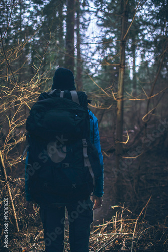 backpacker hiking in dark winter forest at dusk rear view stock