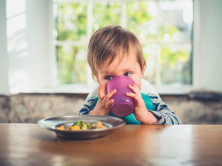 Little boy at table drinking from cup