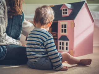 Mother and son playing with doll house