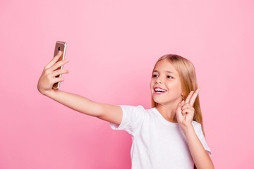 Model people education freetime hobby selfie shots pre teen dream concept. Portrait of cute sweet lovely dreamy careless excited cheerful girl taking selfie on telephone isolated on pink background