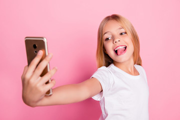 Addiction lifestyle leisure style trend play game concept. Close up portrait of cute lovely sweet charming with toothy smile taking selfie girl on mum's phone isolated on pink background