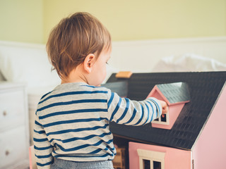 Little boy playing with doll house