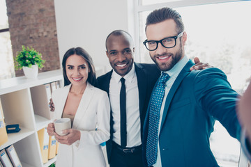 Self portrait of three partners, bearded man in glasses making selfie on front camera with his colleagues in classic suits, holding mug with tea in hand, standing in work place, station