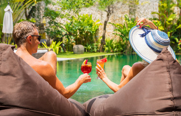 Couple having cocktails on vacation by the pool