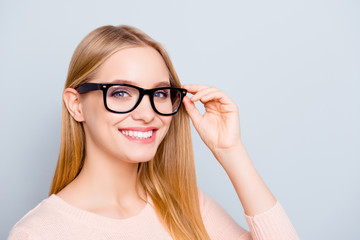 Half-turned portrait of confident smart clever intelligent experienced beautiful with toothy beaming smile freelancer entrepreneur correcting fixing glasses isolated on gray background copy-space