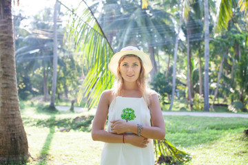 A beautiful young woman stands in a palm grove in the rays of the morning sun, holds a book. Phangan, Thailand