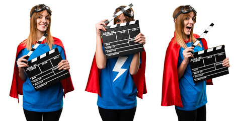 Pretty superhero girl holding a clapperboard
