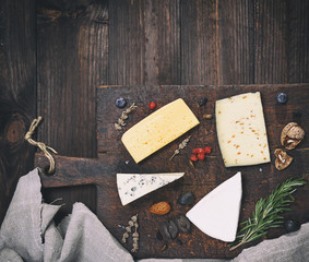 pieces of different cheeses on a brown wooden board: brie, roquefort, cheese with nuts