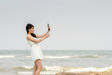 Happy beautiful woman using smartphone for selfie on the beach.