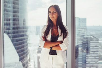 Portrait of elegant business lady wearing white formal suit standing near window looking at camera