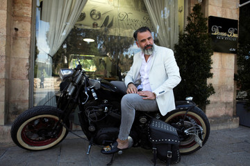 Israeli hair designer Doron Bar, 42, sits on his motorcycle in front of his hair saloon, near Jerusalem's Old City