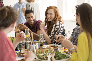Smiling red-haired woman eating dinner