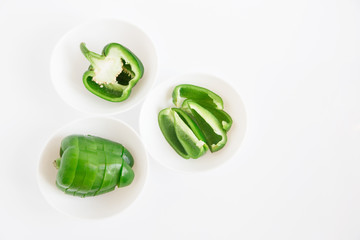 Sliced bell pepper on the white plates.fresh green vegetable.white background.minimalistic styling image