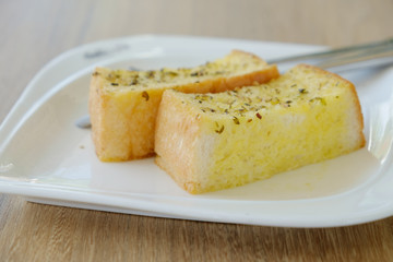 Delicious Garlic bread on white plate.