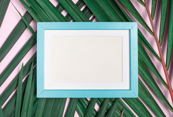 Top view blank blue pastel photo frame on green palm leaf on pastel pink table top background.Summer vacation backdrop.Mock up for display design and text.