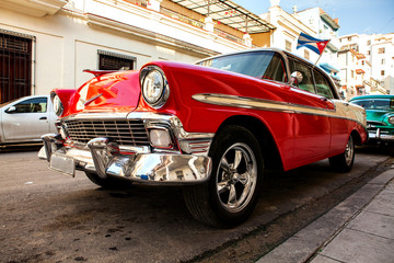 Cuba, Havana: American classic car with cuba flag parked on the street