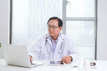 Portrait of senior doctor sitting at his desk in medical office