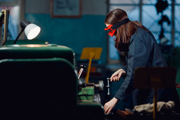 Young woman engineer behind stunt cnc in goggles stands in shop floor factory. Concept industrial procession.