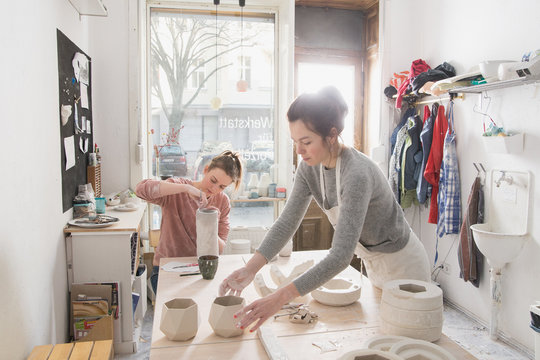 Two ceremic artists are working on their ceramics in a pottery workshop.