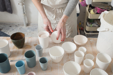 A ceremic artist is putting the finished ceramic products on the table in a pottery workshop.