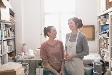 Two smiling ceramic artists portrayed in their pottery workshop.