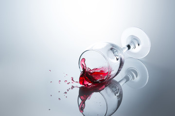 Red wine spilled out of a falling glass with reflection on the surface