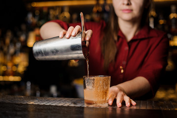 Female mixoligist pouring a fresh drink from shaker into a glass
